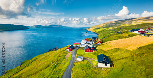 Green summer view from flying droneof Kirkjubour village with Hestur Island on background. Attractive morning scene of Faroe Islands, Denmark, Europe. Beauty of nature concept background.