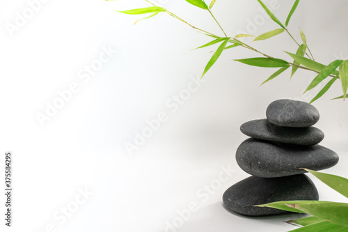 Fototapety, obrazy: Spa zen basalt stones and green bamboo leaves on white background. The concept of wellness, relaxation, massage and well-being. Still life background. Harmony and balance.