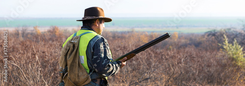 Papel de parede Hunter man in rural field with shotgun and backpack during hunting season