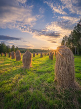 Old-fashioned Style Haystacks With Beautiful Golden Sunset And Sunlight At Warm Summer Evening In Finland