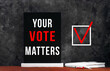 Leinwandbild Motiv Your Vote Matters text sign on black chalkboard with white notebok and red pen on dark background. Message written on blackboard display. Vote elections concept. Make the political choice.