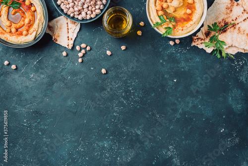 Fotografia Chickpeas hummus, olive oil, raw chickpeas, smoked paprika, pita on dark background