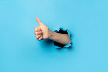 Hand Makes Thumbs Up Gesture On Blue Background. The Gesture Is All Good, Like