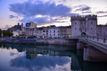 Cityscape Of The Historic Town Of Verdun In The Northeast Of France Before Sunset, River Meuse (Maas) In Front, Medieval Toll Gate On The Right, Cloudy Evening Sky In Summer, Panoramic View