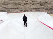 A Guy Rides A Skateboard Pushing Off With One Foot In A Concrete Rollerdrome Against A Stone Wall