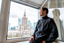 Young Happy Man Looking In Flat Apartment At View Of Warsaw, Poland Famous Palace Of Science And Culture Building Through Window