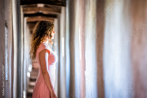 Cuadros en Lienzo Young woman in pink dress side profile standing looking through window of wall o