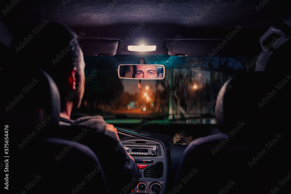Fototapeta man inside the car, strolling through the city. Taxi taking a ride. bright lights to the city.