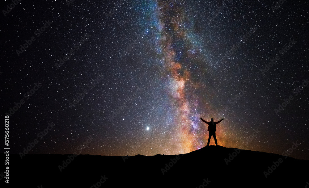 Fototapeta Man in front of the universe with his arms raised