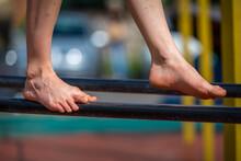 Balancing Bare Feet On A Pole