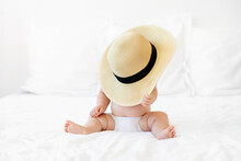 Funny Baby Sitting On White Bed Hidden Under A Straw Hat