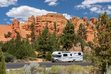 Red Canyon, UT, USA: White Rv Travels On A Tarred Road Through Red Rock Country. Pinnacles And Hoodoos Are Visible In The Background Surrounded By Pine Trees.