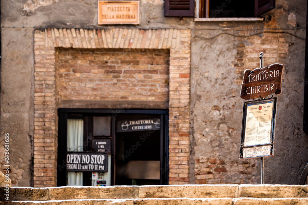 San Gimignano, Italy - August 27, 2018: Street in town village in Tuscany during summer day and open sign with menu for trattoria chiribiri restaurant