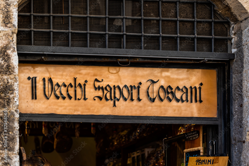 San Gimignano, Italy - August 27, 2018: Town village in Tuscany with wine store sign il vecchi sapori toscani closeup and nobody
