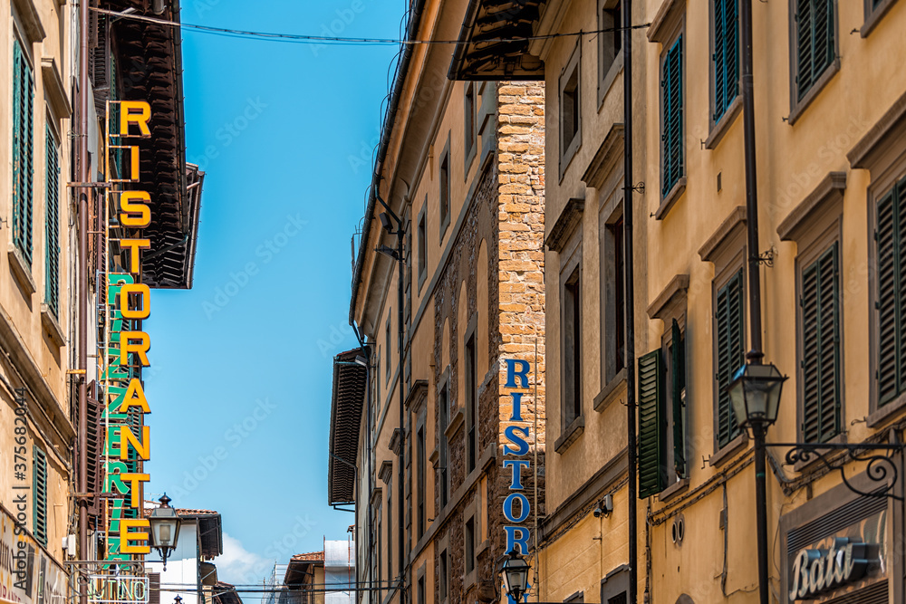 Firenze, Italy - August 30, 2018: Outside exterior of Florence building in Tuscany on alley street with vertical sign for restaurant ristorante