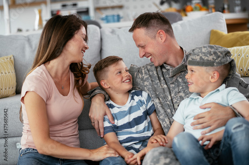 Happy soldier sitting on the floor with his family Wallpaper Mural