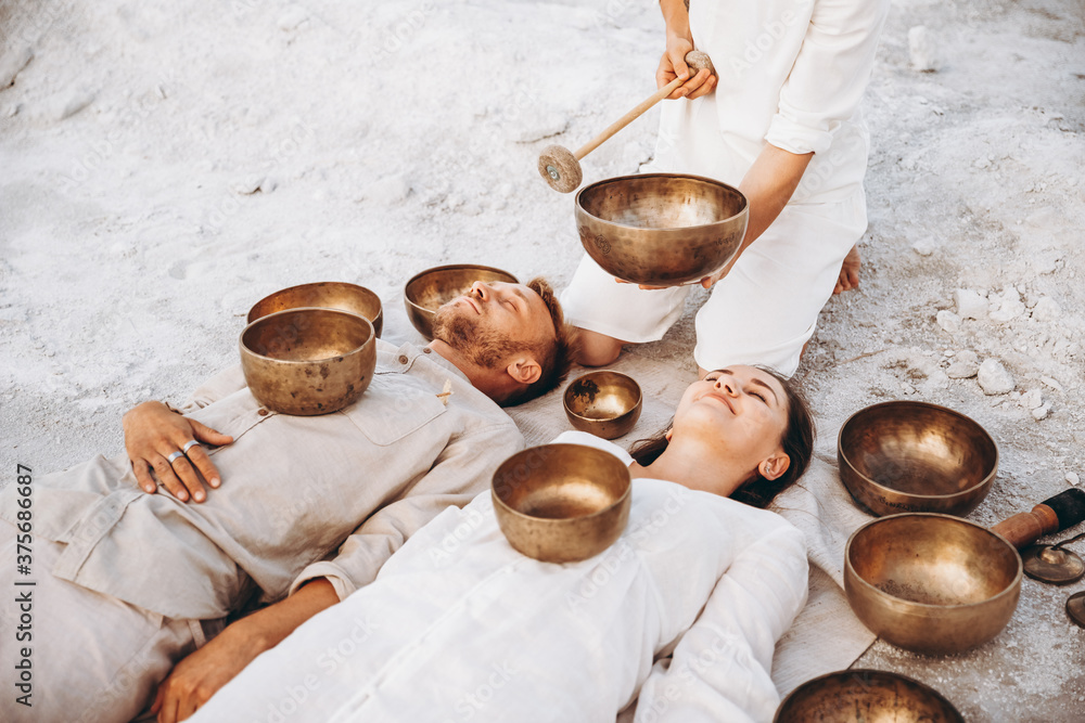 Fototapeta 01.06.2019 Vinnitsa, Ukraine: group therapy with Tibetan singing bowls for a girl and a boy lying on the ground in the middle of the desert surrounded by copper bowls, meditation and relaxation