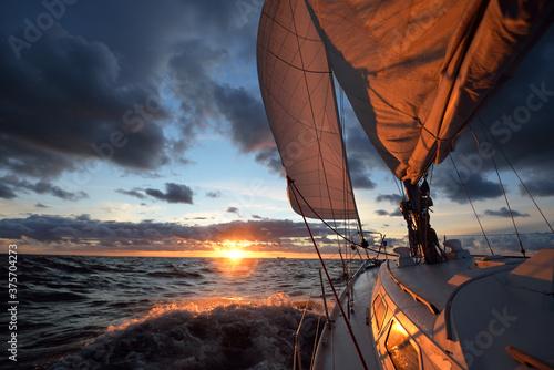 Fototapeta Yacht sailing in an open sea at sunset