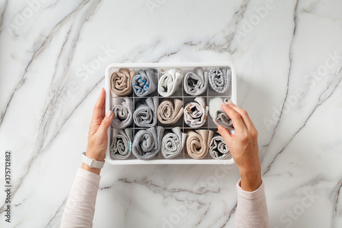 Woman hands placing organizer drawer divider with full of folded underwears and socks.
