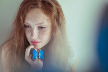 Beautiful Young Redhead Woman With Freckles Holding A Blue Butterfly