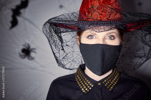 Fotografiet Woman with Halloween witch costume wearing red hat and protection mask