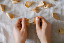 """Hands Holding Fortune Cookie Message Reading """"""""happiness"""""""""""