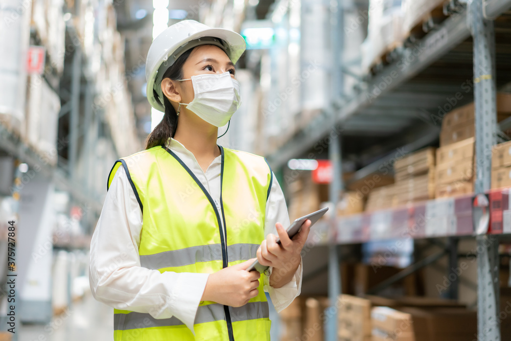 Fototapeta Young asian woman auditor or trainee staff wears mask working during the COVID pandemic in store warehouse shipping industrial. looking up and checks the number of items store by digital tablet.