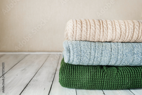 stack of knitted warm sweaters in pastel colors on light wooden table in the roo Fototapet