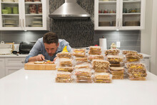 Man Fixing A Lot Of Sandwiches