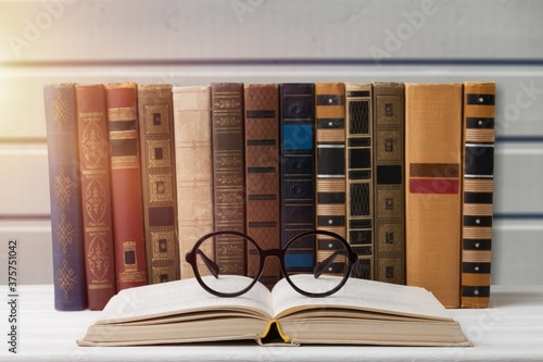 Tela A stack of books with glasses for reading on the desk