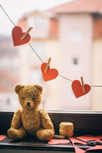 Old Teddy Bear And Red Hearts Hanged By The Window