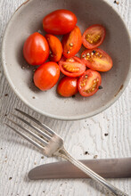 Closeup Cherry Tomatoes In Bowl With Knife And Fork