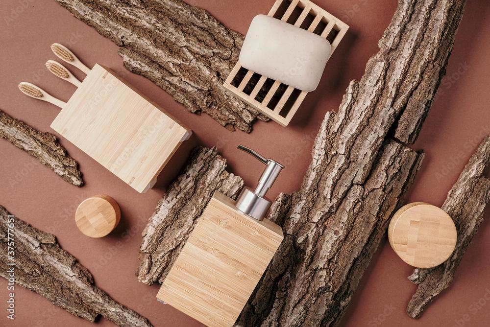 Fototapeta Bamboo bath accessories - soap dish, soap dispenser, tooth brush, organic dry shampoo for personal hygiene on wooden bark texture. Biophilic design concept. Zero waste, plastic free, sustainable
