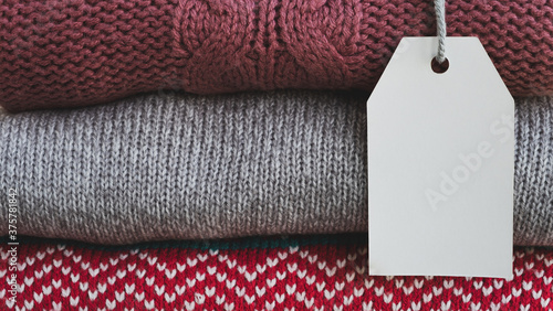 Knitted sweaters with empty card for price or text Fototapeta