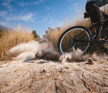 Details Of A Mountain Bike Racing And Blowing Out Dirt On A Curve.