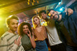 Smile. Portrait of young men and women looking at camera and smiling. Multiracial group of friends hanging out at party in the bar