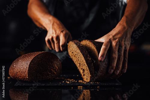 Photo Man cutting whole grain bread on a stone board, dark background