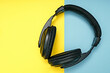 canvas print picture - Large, black headphones lie on a colored background. Device for individual listening to music.