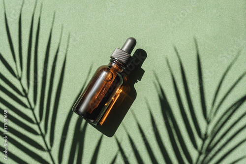 Fotografia top view of Blank amber glass essential oil bottle with pipette on green background with tropical leaves shadows