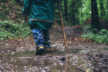 Young Boy With Yellow Gumboot Running Through A Puddle Of Mud In The Forest