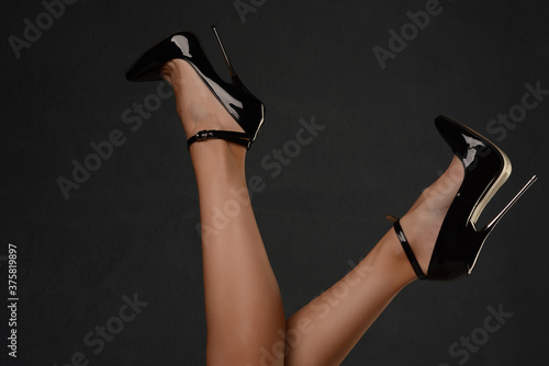 Photographie Slender female legs in a fetish shoe with extremely high heels.