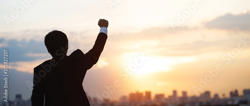 Fotografiet silhouette hand raised fist business man with sun lighting in morning