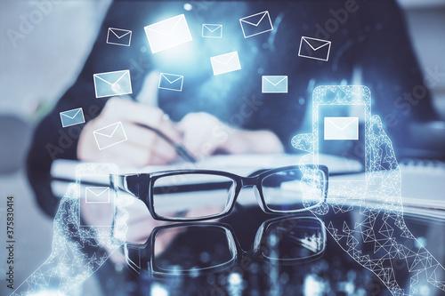 Fototapeta E-mail envelop theme hologram over hands taking notes background