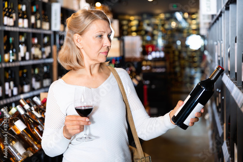 Fototapeta Portrait of glad positive smiling mature woman tasting red wine while visiting w