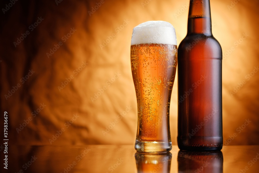 Fototapeta Ice cold pint of beer in a bottle and glass
