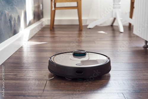 Close up of Robotic vacuum cleaner on laminate wooden floor cleaning in the kitchen Canvas