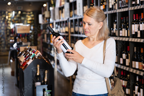 Fotografía Portrait of mature woman visiting winehouse in search of bottle of good wine