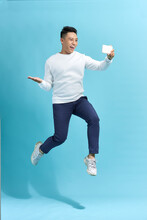 Full Length Portrait Of Happy Man Jumping And Screaming While Taking Selfie On Smartphone Over Blue Background