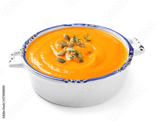 Tasty creamy pumpkin soup in bowl on white background