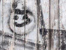 Smiley Face Sprayed On Decaying Wooden Wall